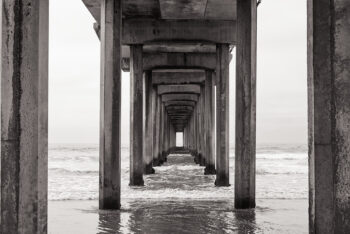 Black and White image of La Jolla Pier with the gentle ocean waves beneath it. Limited edition print by Rick Ryan. Purchase your large, framed wall decor.